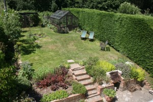 lovely secluded garden at The Pink House Lulworth with large lawn area, BBQ and surrounding nature for all to enjoy